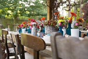 Set rustic wooden table decorated with autumn flowers outdoors