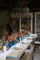 Rustic wooden table set with autumn flowers on roofed terrace