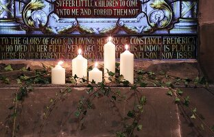 Candles burning in front of a gravestone