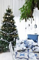 Christmas dinner table set in blue and white in front of Christmas tree