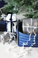 Gifts in blue baskets below Christmas tree