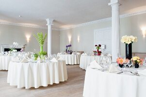 Tables festively set for wedding in room with white columns