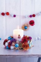 A brightly coloured glittery Advent wreath decorated with chocolate suns and glittery pompoms