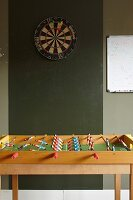 Table football table below darts board on green wall