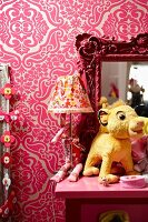Soft toy, table lamp and framed mirror on pink table against wall with patterned wallpaper