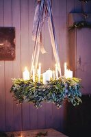 A hanging Advent wreath made from green twigs and pine spigs with white pillar candles