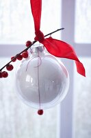 A white Christmas tree bauble decorated with a red ribbon and a sprig of holly berries