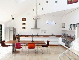 Minimalistischer Tisch mit Holzplatte und Stühle mit verschiedenen Bezügen in offener Designerküche