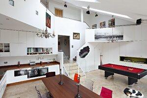 Blick über Essplatz und Einbauküche auf Billardtisch in nach oben offenem Raum mit umlaufender Galerie