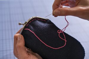 A purse frame being sewn on with staying stitch