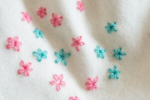 Flowers embroidered in lazy daisy stitch on a woollen blanket