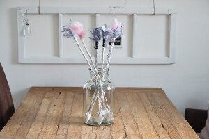 Hand-made arrows with coloured feather flights in retro glass jar on wooden table