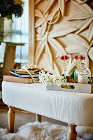 Champagne and raspberries in crystal glasses on tray on ottoman