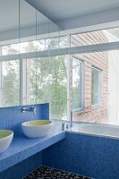 Mirrored cabinets, blue mosaic tiles and glass wall in bathroom