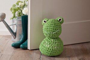 Crocheted frog doorstop on wooden floor