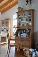 Table lamp on stripped wooden bureau and cane chair in open-plan country-house interior