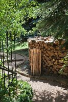 Firewood stacked next to curved gravel path in garden