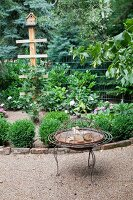 Vintage fire bowl on gravel path in front of edged flowerbed with nesting box on post