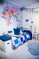 Map of world and patchwork bed cover in child's bedroom in shades of blue