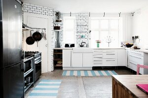 White kitchen counter, black fridge-freezer and cooker and striped rugs