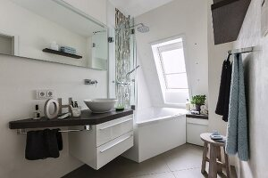 A small, comfortable bathroom with a whirlpool bathtub under a sloping ceiling
