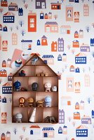Various toys in display case on patterned wallpaper
