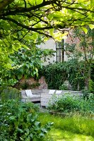 View of seating area against climber-covered brick wall in green garden