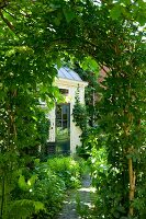 View of traditional house through trellis arch in garden