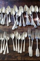 Silver cutlery lined up on rustic wooden table