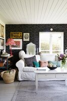 Sofa, white coffee table and wall covered in black and white wallpaper in romantic Swedish cabin