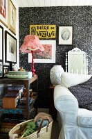 Pink table lamp on vintage wooden shelves and sofa against black and white patterned wallpaper