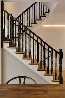 Elegant, restored wooden staircase with black-painted bannisters and indirect lighting