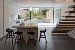 White, designer kitchen with island counter, staircase and glass wall with garden view