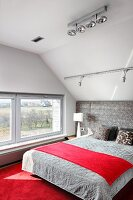 Attic bedroom with red carpet and upholstered headboard