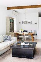 Kastenförmiger Couchtisch aus dunkelfarbigem Holz mit Schubladen und helles Sofa in offenem Wohnraum, im Hintergrund Essplatz in Zimmerecke
