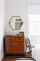 Vintage-Kommode vor polygonalem Spiegel in Schlafzimmerecke