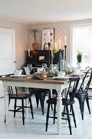 Festively set table and various black chairs