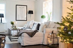 Fairy lights on Christmas tree in front of white sofa with many scatter cushions