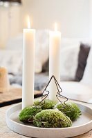 Two lit candles, moss and metal Christmas on tray