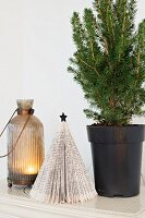 Small potted conifer next to origami Christmas tree