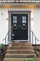 Steps leading to black double front doors of white house decorated with twin wreaths