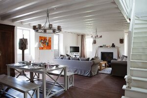 Country-house-style benches and table painted grey and living area in open-plan interior