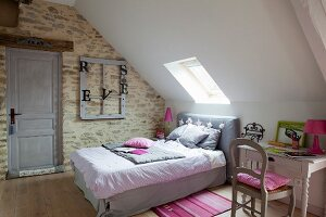 Double bed below skylight in sloping ceiling and vintage-style desk in bedroom with stone wall
