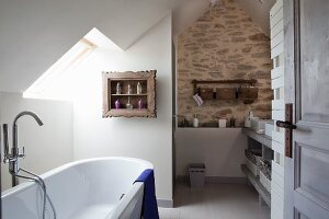 White bathtub under skylight in sloping ceiling in bathroom with stone wall