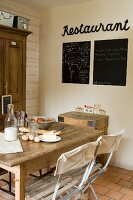 Breakfast ingredients on table next to blackboards and motto on wall in vintage-style dining area