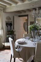 Set dining table and loose-covered chairs in rustic interior