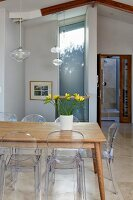 Vase of yellow freesias on wooden table, Ghost chairs and delicate pendant lamps with glass lampshades in modern interior