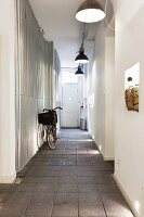 Bicycle on paved floor in narrow hallway with industrial-style pendant lamps