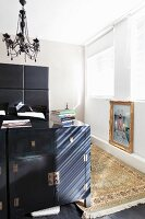 Black half-height cabinet at foot of bed with tall headboard below postmodern pendant lamp