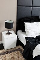Table lamp with black lampshade on white bedside cabinet next to bed